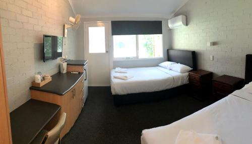 A bed or beds in a room at Bateau Bay Hotel