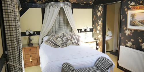 A bed or beds in a room at The Old Priory B&B