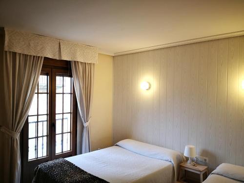 Cama o camas de una habitación en Hostal Alcántara