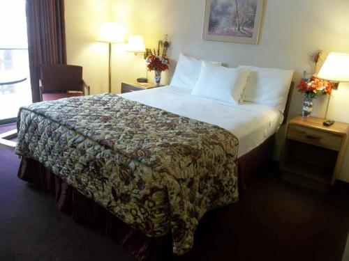 A bed or beds in a room at Carriage House Motor Inn