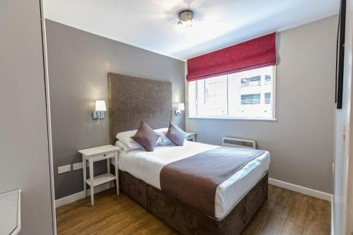 A bed or beds in a room at High Street Townhouse Aparthotel