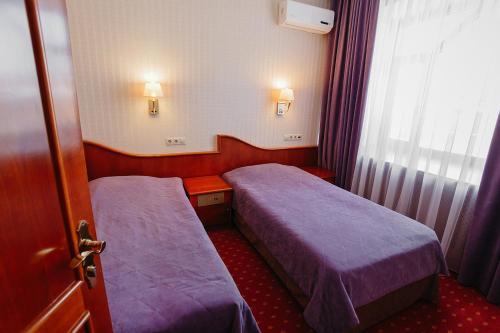 Кровать или кровати в номере Бизнес отель Нефтяник на Толстого