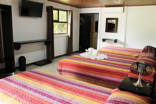 A bed or beds in a room at Hotel Arenal Country Inn