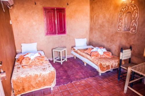 A bed or beds in a room at La Baraka Auberge