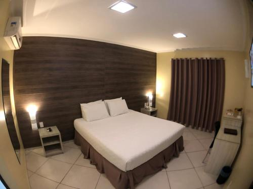 A bed or beds in a room at Garoto Park Hotel