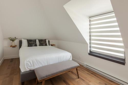 A bed or beds in a room at Les Lofts Ste-Anne