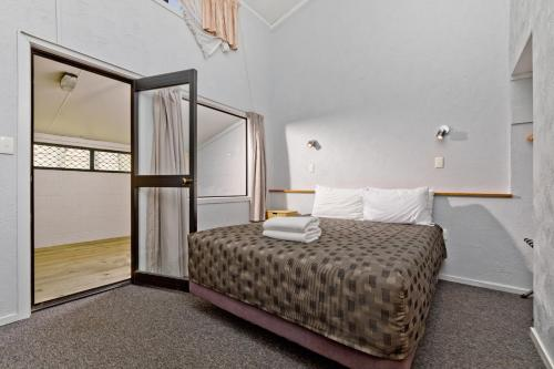 A bed or beds in a room at Oakwood Manor Motor Lodge