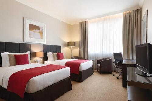 A bed or beds in a room at Ramada Downtown Abu Dhabi
