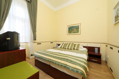 A bed or beds in a room at Hotel Blaha Lujza