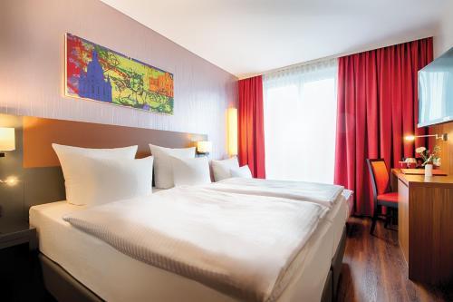 Ein Bett oder Betten in einem Zimmer der Unterkunft Leonardo Hotel Dresden Altstadt