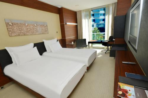 A bed or beds in a room at Swissôtel Grand Efes Izmir