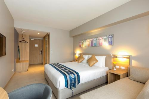 A bed or beds in a room at Oakwood Hotel Journeyhub Phuket