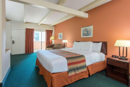 A bed or beds in a room at Days Inn by Wyndham St. Louis North