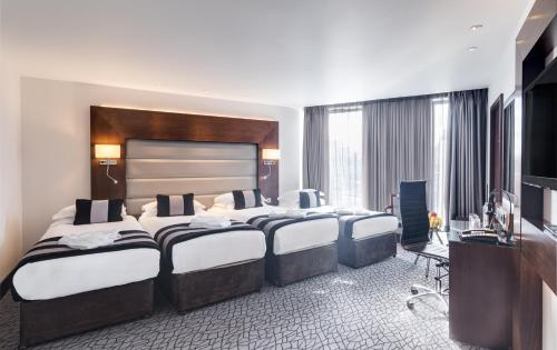 A bed or beds in a room at Park Grand London Heathrow