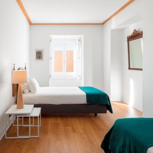 A bed or beds in a room at Palácio Camões - Lisbon Serviced Apartments