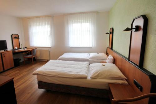 A bed or beds in a room at Hotel & Restaurant am Rosenhügel