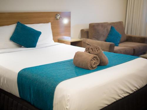 A bed or beds in a room at Sunnybank Star Hotel