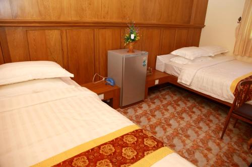 A bed or beds in a room at Sule Sapphire Inn