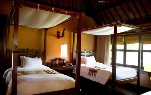 A bed or beds in a room at Hotel Tugu Bali