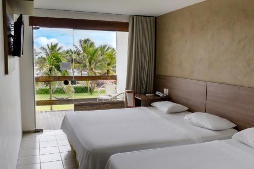 A bed or beds in a room at Villa da Praia Hotel