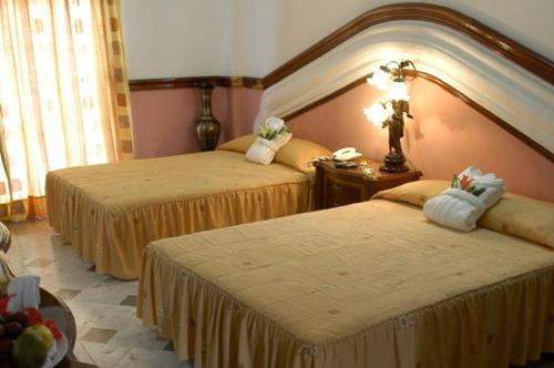 A bed or beds in a room at Canadian Resort Huatulco