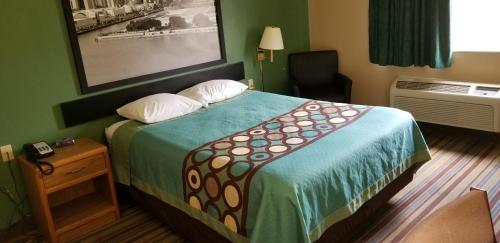 A bed or beds in a room at Super 8 by Wyndham Pontoon Beach IL/St. Louis MO Area
