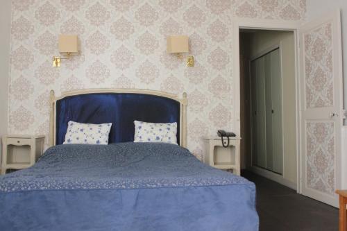 A bed or beds in a room at Hôtel De La Banniere De France