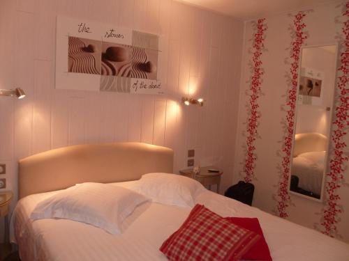 A bed or beds in a room at Citotel Hotel Restaurant Les Pins