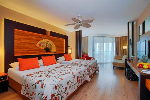 A bed or beds in a room at Limak Lara De Luxe Hotel