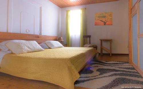 A bed or beds in a room at Hostal Colina de Lluvia