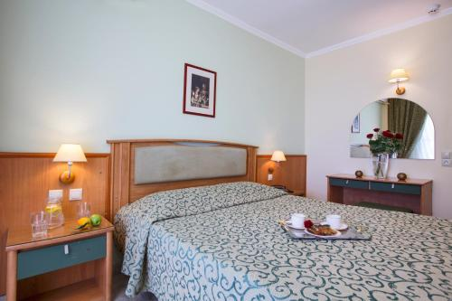 A bed or beds in a room at Tolon Holidays Hotel