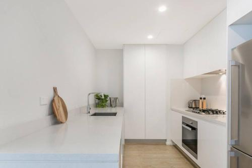 A kitchen or kitchenette at 2Bed Apt in Macquarie Park Walk Station NNR306