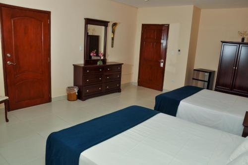 A bed or beds in a room at Allamanda Hotel