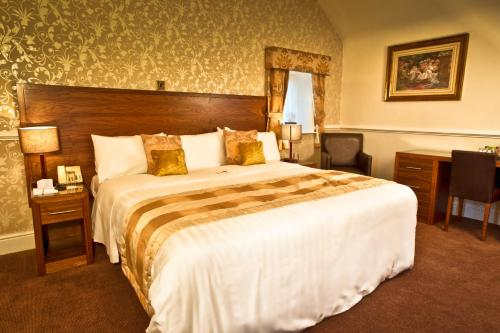 A bed or beds in a room at Bagden Hall Hotel