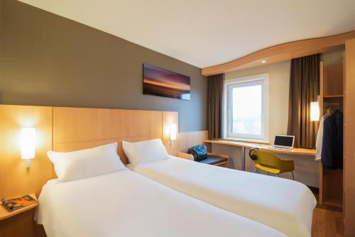 A bed or beds in a room at ibis Rotterdam Vlaardingen