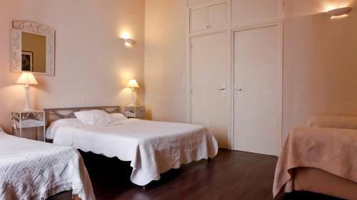 A bed or beds in a room at Hôtel des Facultés