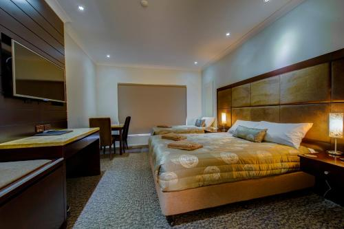 A bed or beds in a room at Western Downs Motor Inn