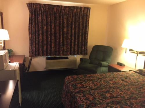 A bed or beds in a room at Haven Inn & Suites