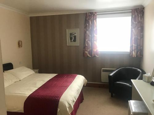A bed or beds in a room at Empire Travel Lodge