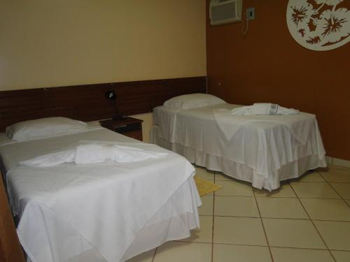 A bed or beds in a room at Hotel da Gaúcha