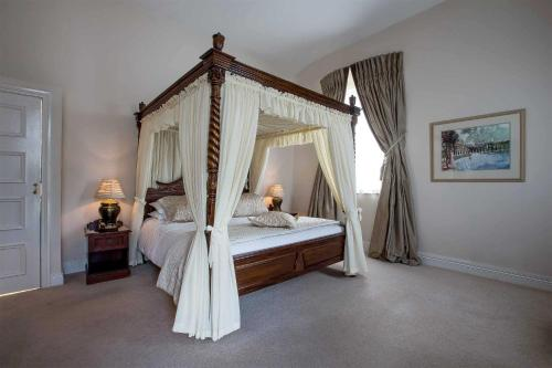 A bed or beds in a room at Tullyglass House Hotel
