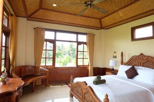 A bed or beds in a room at Ganesha Ubud Inn