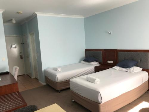 A bed or beds in a room at Springwood Motor Inn