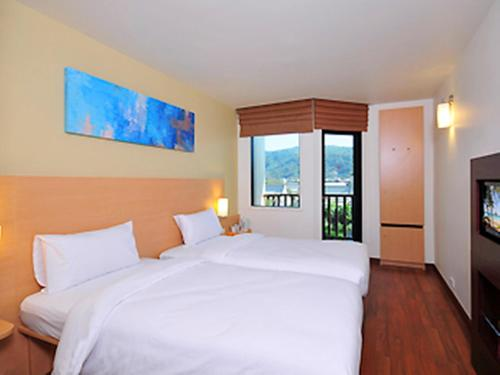 A bed or beds in a room at Ibis Phuket Kata