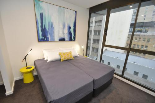 A bed or beds in a room at Orange Stay Sydney CBD