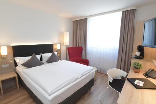 A bed or beds in a room at Best Western Queens Hotel Pforzheim-Niefern