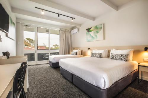A bed or beds in a room at Nightcap at Seaford Hotel