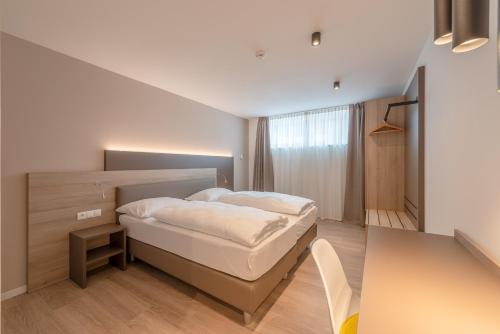 A bed or beds in a room at Residence Garni Hotel Vineus