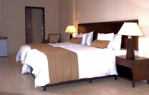 A bed or beds in a room at Hotel Royal Kinshasa