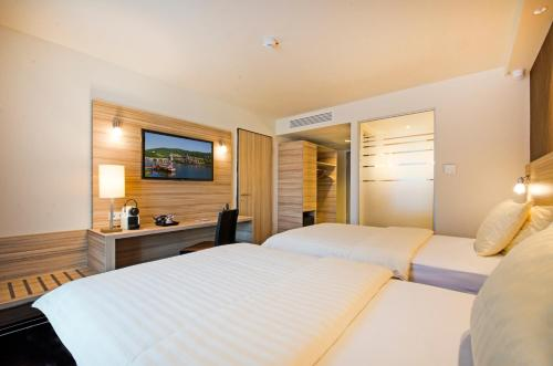 A bed or beds in a room at Star Inn Hotel & Suites Premium Heidelberg, by Quality